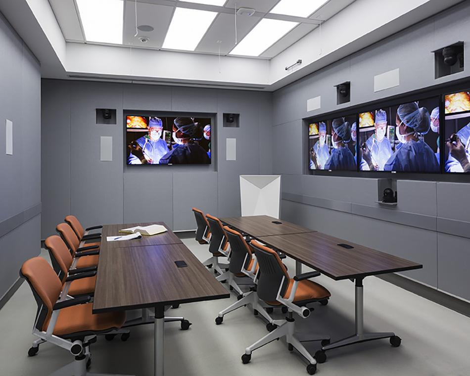 Monitors in the Conference Room show a simulated operation.